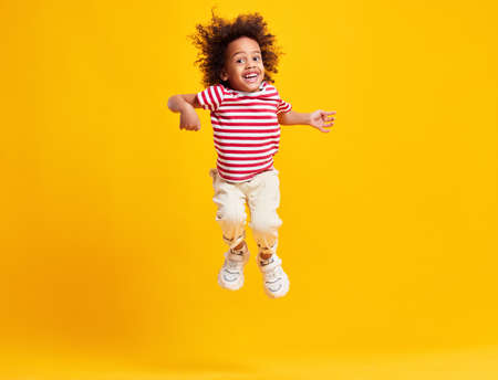 Full length of energetic expressive little ethnic boy with Afro hairstyle in stylish casual outfit jumping with raised arms and looking down against yellow background