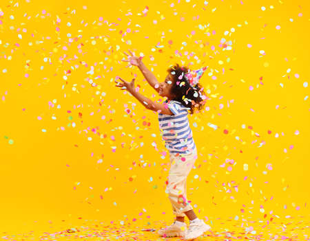 Joyful little black child with Afro hair laughing and jumping while trying to catch colorful confetti during the birthday celebration against yellow background