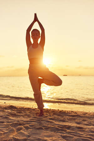 Healthy fit woman doing Tree Pose with hands above head while standing on beach against sky with sunset