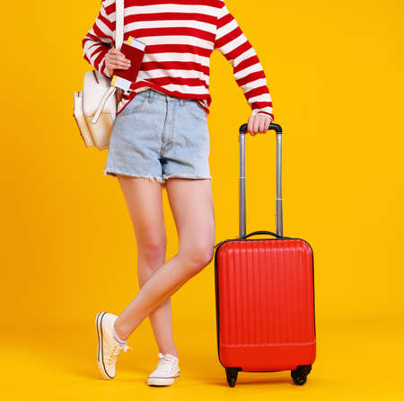 Ð¡oncept of summer traveling. Ð¡ropped female legs in shorts, passport, ticket and red suitcase on a bright yellow background