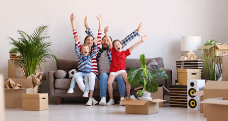 Full body optimistic parents and kids raising arms and screaming in excitement while sitting on couch in new flat