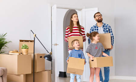 Amazed parents and children with carton boxes looking around in amazement while entering new flat during relocation