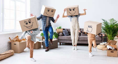 Carefree parents and kids in carton boxes on heads dancing in new spacious flat while having fun and enjoying relocation together Foto de archivo