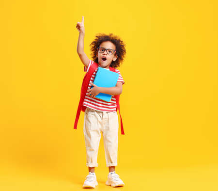 Cheerful smart African American little schoolboy with curly hair in casual clothes and eyeglasses looking at camera while having idea standing against yellow background with notebooks