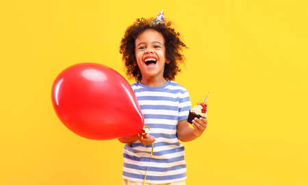 Cheerful cute little African American boy with curly hair in casual clothes laughing and looking at camera while standing against yellow background with red balloon and birthday cupcake in hands
