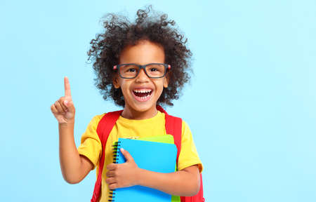 Cheerful smart African American little schoolboy with curly hair in casual clothes and eyeglasses smiling and and looking at camera while having idea standing against blue background with notebooks