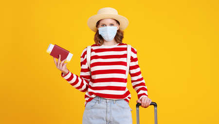 Excited young female tourist with suitcase in casual clothes hat and face mask holding passport and ticket in hand and looking at camera with happiness against yellow background