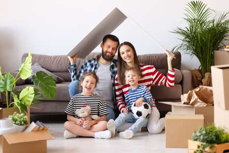 Cheerful parents and kids holding house roof over head and smiling for camera while sitting near couch and belongings in new flat