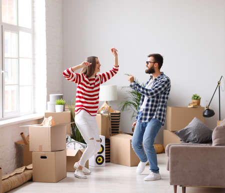 Full body side view of delighted young man and woman jumping happily while having fun during moving into new apartment
