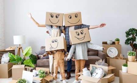 Unrecognizable couple and kids wearing carton boxes on heads standing together in new flat with various stuff during relocation