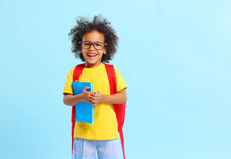 Positive little African American boy with curly hair in casual clothes and eyeglasses smiling while standing against blue background with school backpack and copybooks Foto de archivo