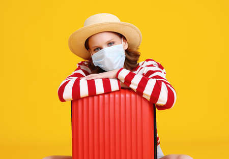 Excited young female tourist with suitcase in casual clothes hot and face mask looking at camera and preparing for vacation