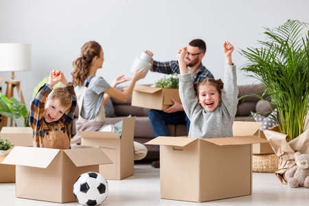 Delighted playful siblings sitting in carton boxes with raised arms and enjoying relocation in new flat on background of parents sitting on sofa