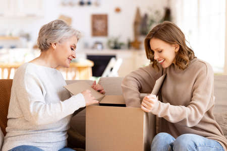 Positive curious young woman with middle aged mother sitting on sofa and unpacking cardboard box with ordered purchases while spending time together at home