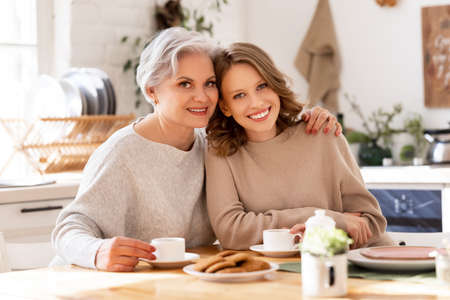 Happy mature gray haired woman embracing smiling young daughter while having morning coffee together in cozy home kitchen