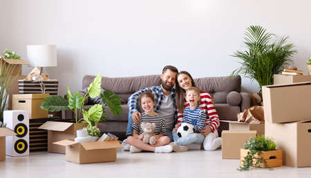 Delighted parents and cute kids gathering on floor in living room with unpacked boxes in new flat and looking at camera