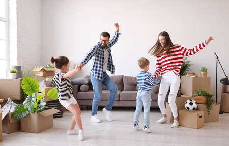 Full body family: mother and father holding hands and dancing with daughter and son near couch and carton boxes with belongings in new Foto de archivo