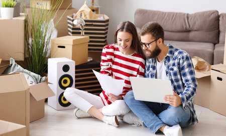 Happy young couple with laptop and papers sitting on floor in room with packed boxes and discussing insurance contract after relocation into new apartment