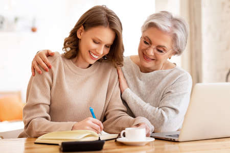 Young female in casual clothes taking notes in planner while helping elderly mother working remotely on laptop