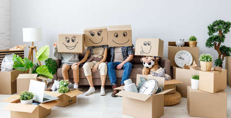Unrecognizable happy family: couple and kids wearing carton boxes on heads sitting together in new flat with various stuff during relocation Banco de Imagens