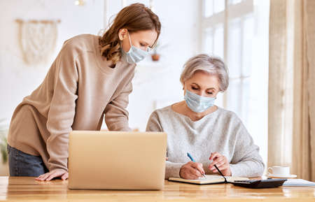 Unrecognizable elderly female in casual clothes and mask taking notes in planner while viewing information in internet with young daughter working remotely on laptop