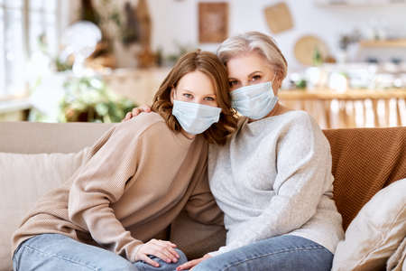Anonymous young female in casual clothes and face mask sitting on sofa hugs elderly mother and looking at camera at home