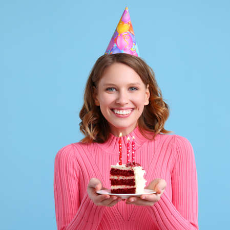 Happy female in sweater and party hat holding cupcake with candle and looking at the camera with smile while during birthday celebration