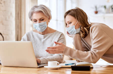 Anonymous serious young woman in casual clothes and face mask pointing at screen of laptop while helping elderly mother working remotely at home during coronavirus pandemic Foto de archivo