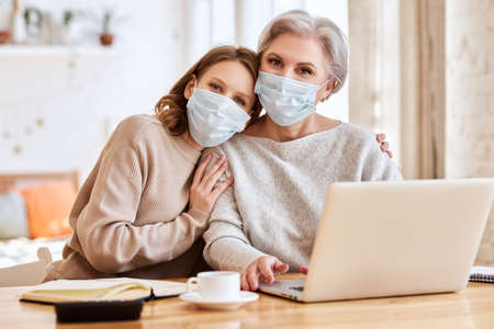 Anonymous young woman in casual clothes and face mask lovingly hugs the elderly mother, while helping her working remotely and looking at camera at home