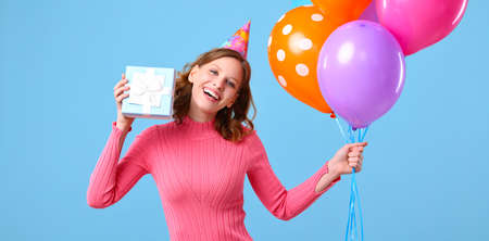 Delighted young female smiling and looking at camera while showing bunch of colorful balloons and wrapped birthday present against blue background