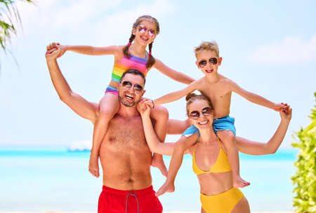 Cheerful parents carrying son and daughter on shoulders while laughing and looking at camera on ocean shoreline