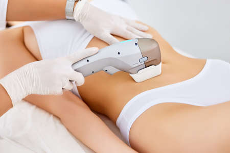 Crop anonymous beautician in gloves using laser hair removal apparatus on bikini zone of female client during beauty procedure in modern salon Foto de archivo