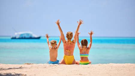 Back view of woman with daughter and son in colorful swimsuits raising arms while sitting on sandy beach of exotic ocean shore