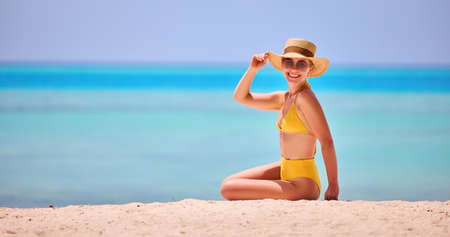 Happy female in trendy two pieces swimsuit and straw hat with sunglasses smiling at camera while sitting on sandy beach