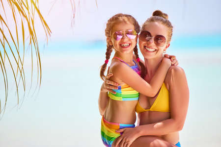 Happy woman and charming girl in colorful swimwear and sunglasses looking at camera happily on blurred background of ocean Foto de archivo