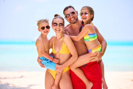 Laughing parents with boy and girl in vivid swimsuits smiling at camera standing on tropical shoreline