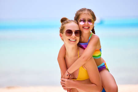 Happy woman giving piggyback ride to laughing girl both wearing vivid swimsuits with sunglasses and looking at camera on seashore