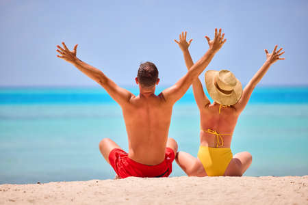 Back view of happy couple: man and woman in swimsuits raising arms above head while sitting on coastline of ocean in sunlight