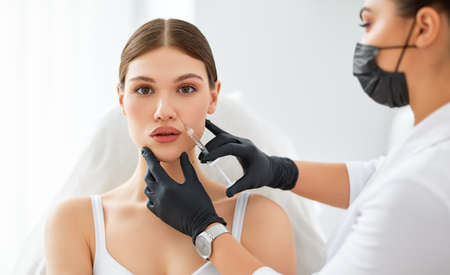 Professional beautician in protective mask and gloves applying injection on face of young female client during cosmetology treatment in beauty clinic Foto de archivo