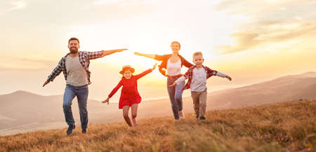 Happy family: mother, father, children son and daughter running on nature on sunset Foto de archivo