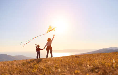 Back view of happy family mother and son launch a kite on nature at sunset Foto de archivo