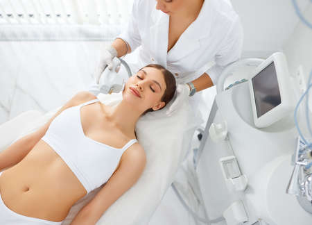 From above of young female client receiving laser lifting of the skin procedure on face during beauty treatment in modern salon