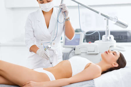 Relaxed young female client receiving professional body contouring treatment with laser tool during appointment in modern beauty clinic Foto de archivo