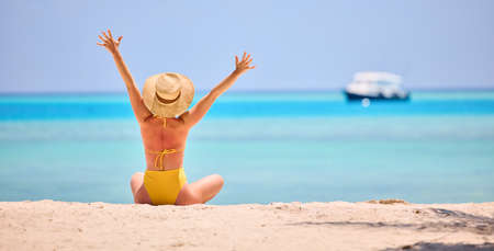 Back view of woman in vivid swimsuit and straw hat raising arms while sitting on sandy shore of turquoise ocean