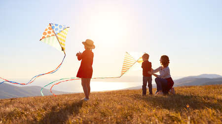 Happy family mother and children launch a kite on nature at sunset