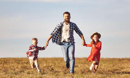 Cheerful young family: mother with little son and daughter in casual clothes having fun and running in field in summer evening Foto de archivo