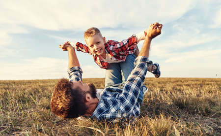Happy family: father lying on autumn grass and throwing up cheerful little son in nature Foto de archivo