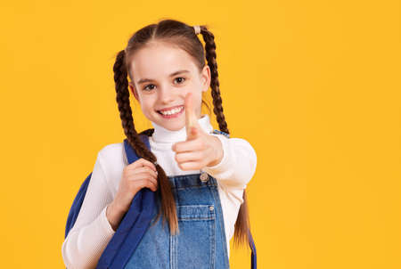 Adorable little schoolgirl with pigtails wearing casual white turtleneck and denim overall carrying backpack and pointing at camera with smile against yellow background Foto de archivo