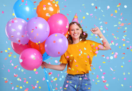 Optimistic woman with colorful balloons smiling and dancing under falling confetti during birthday celebration against blue background