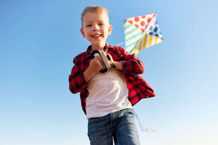 happy kid boy laughing with a kite against the sky outdoors Foto de archivo